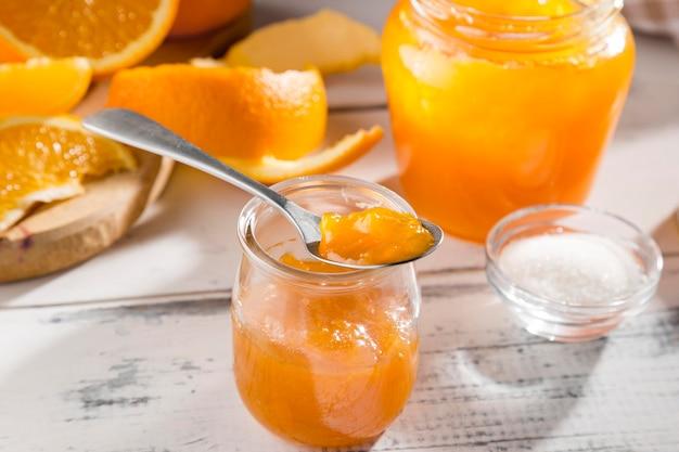 Grande ângulo do frasco transparente com geléia de laranja