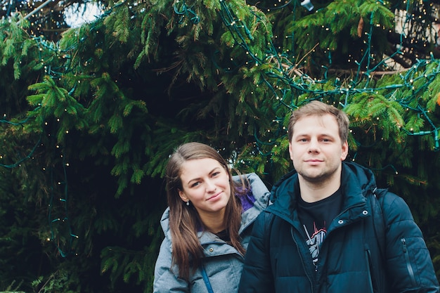 Grande árvore de natal decorada com o jovem casal em pé próximo.