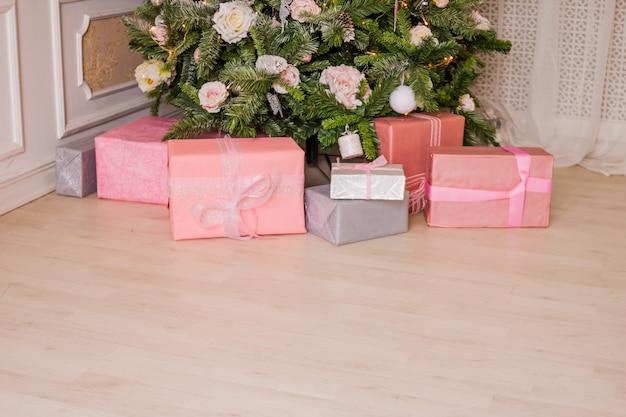 Grande árvore de natal lindamente decorada com enfeites rosa, fitas, flocos de neve e um monte de caixas de presente e brinquedos abaixo