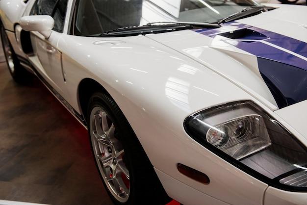 Grande automóvel esportivo branco com linhas azuis estacionado dentro de um salão de automóveis