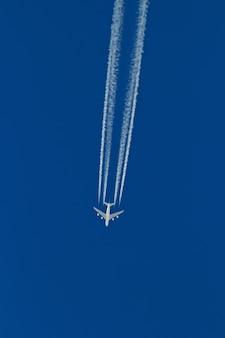 Grande avião de passageiros voa deixando um rastro no céu sem nuvens