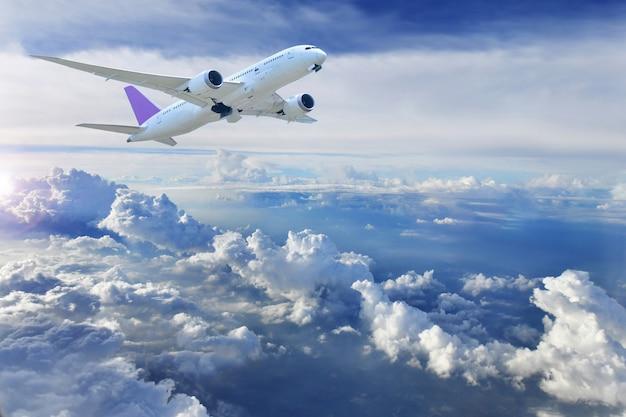 Grande avião voando, com céu azul e nublado.