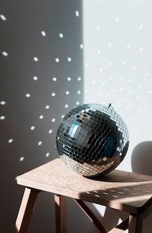 Grande bola de discoteca na cadeira de madeira
