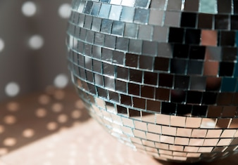 Grande bola de discoteca no chão com luzes de festa