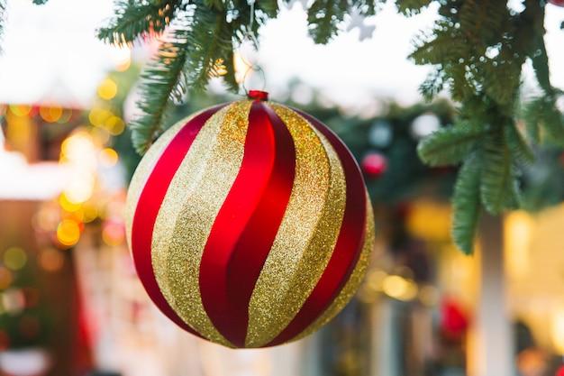 Grande bola de natal, árvore de natal de brinquedo em um galho no fundo de luzes de natal