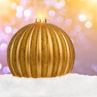 Grande bola de natal dourada na neve sobre fundo desfocado festivo com cópia-espaço