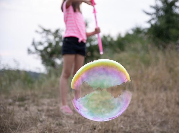 Grande bolha de sabão multicolorido sobre um fundo desfocado.