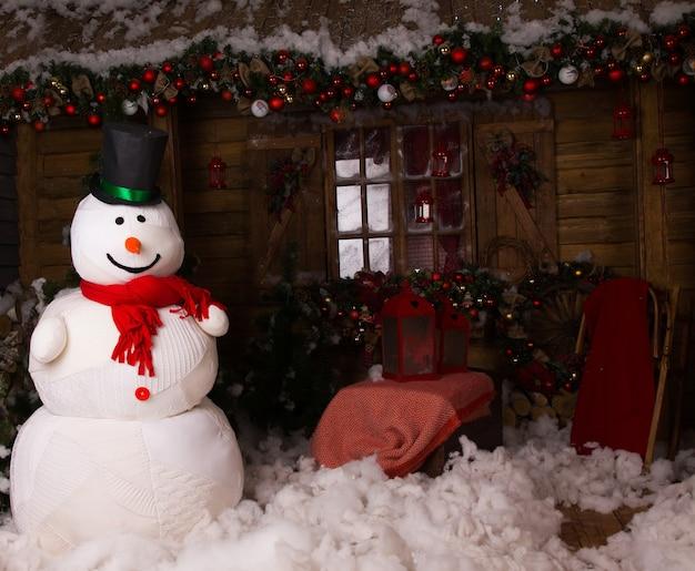 Grande boneco de neve de inverno com boné em pé na casa de madeira decorada com algodão neve no chão.