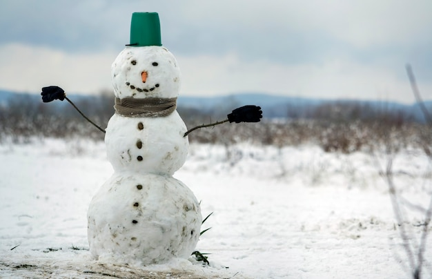 Grande boneco de neve sorridente com balde de chapéu, lenço e luvas na paisagem de inverno de campo nevado branco, árvores pretas turva e fundo de espaço de cópia de céu azul. . feliz natal e cartão de feliz ano novo.
