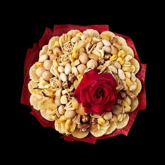Grande buquê composto por frutas exóticas secas e castanhas, decoradas com uma grande rosa vermelha em fundo preto, vista superior