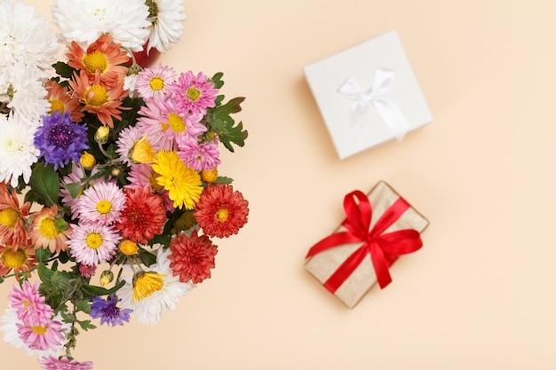 Grande buquê de flores coloridas diferentes e boxex de presente no fundo bege. vista do topo. concentre-se em flores.