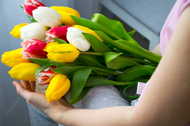 Grande buquê de lindas flores coloridas de tulipas nos joelhos de uma mulher em casa com roupas