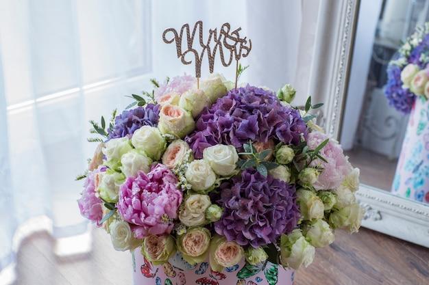 Grande buquê de peônias, rosas e hortênsias em uma caixa de presente e cartas mr. and mrs.