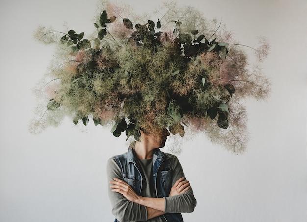 Grande buquê decorativo feito de folhas verdes e musgo paira sobre a cabeça do homem