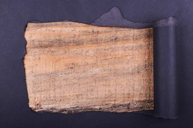 Grande buraco no papel preto. rasgado. fundo de madeira abstrato.