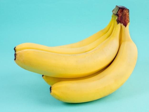 Grande cacho de bananas amarelas maduras no fundo azul brilhante