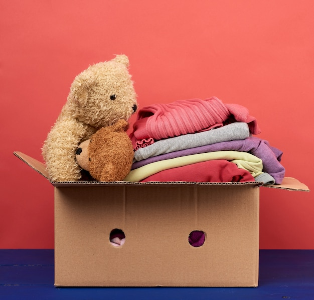 Grande caixa de papelão marrom cheia de roupas e brinquedos infantis
