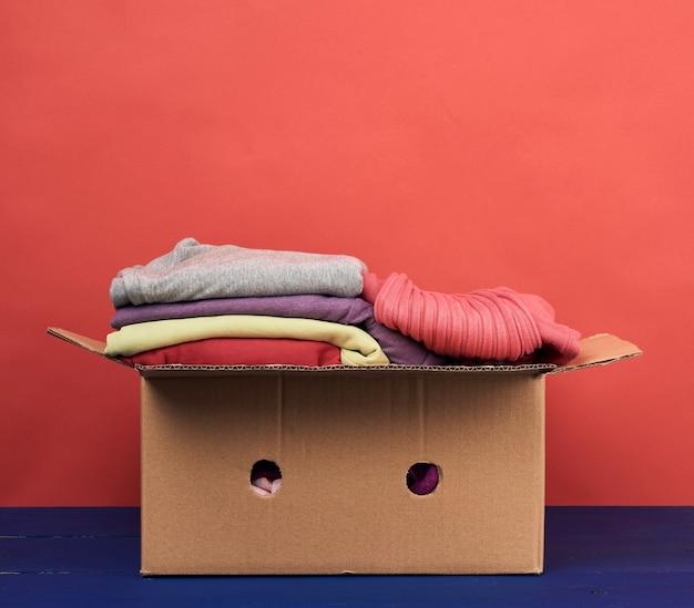 Grande caixa de papelão marrom cheia de roupas