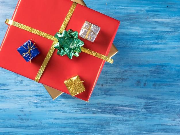 Grande caixa vermelha de presente de natal com caixas menores em fundo azul de madeira vintage. símbolo de celebração.