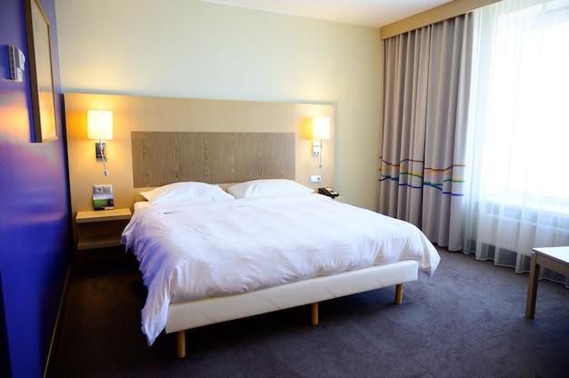 Grande cama de casal branca no quarto