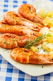 Grande camarão grelhado com batatas cozidas em um prato branco em um restaurante na mesa