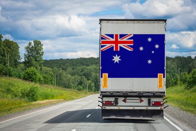 Grande caminhão com a bandeira nacional da austrália, movendo-se na estrada