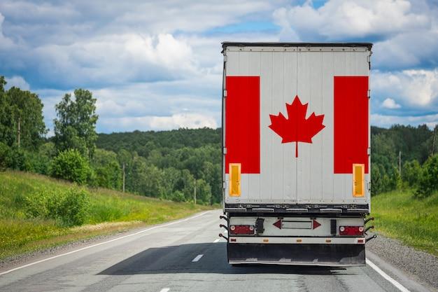 Grande caminhão com a bandeira nacional do canadá, movendo-se na estrada