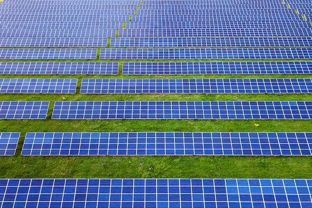 Grande campo do sistema de painéis solares foto voltaicos produzindo energia limpa renovável na grama verde.