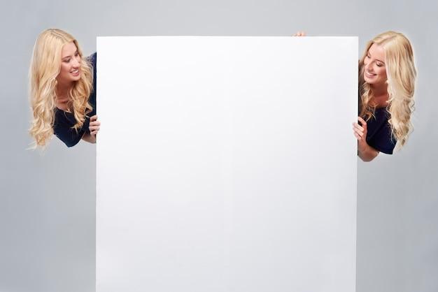 Grande cartaz vazio e duas irmãs