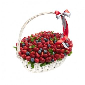 Grande cesta de vime cheia de morangos maduros e mirtilos em um fundo branco