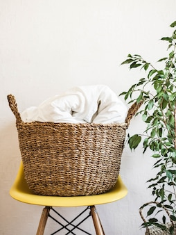 Grande cesta de vime com um cobertor branco em uma cadeira amarela e planta de casa contra uma parede branca.