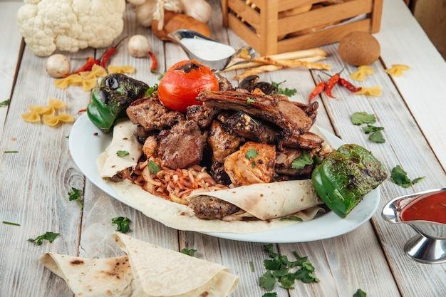 Grande churrasqueira grelhada com diferentes carnes e vegetais