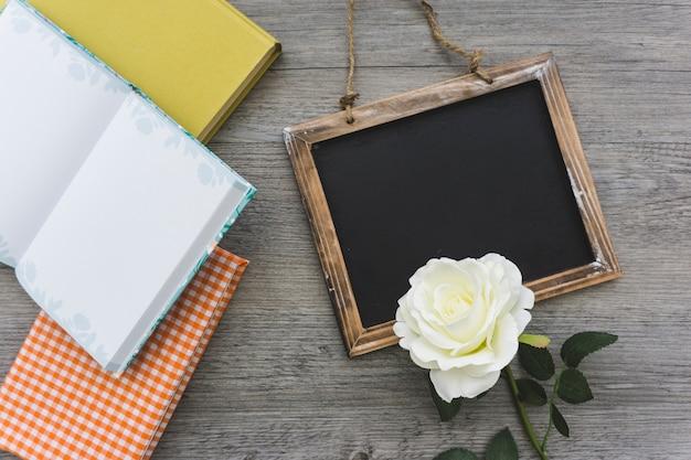 Grande composição com ardósia, livros e flores decorativas