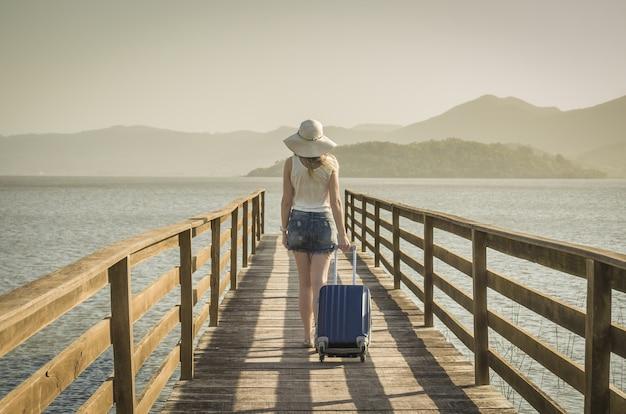 Grande conceito de férias. jovem mulher segurando sua mala, esperando o barco no cais