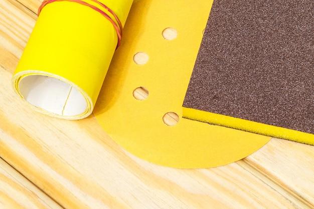 Grande conjunto de ferramentas abrasivas e lixa amarela em placas de madeira