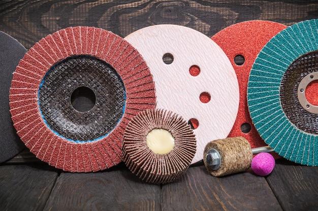 Grande conjunto de ferramentas abrasivas e lixa multicolorida no espaço preto vintage de madeira