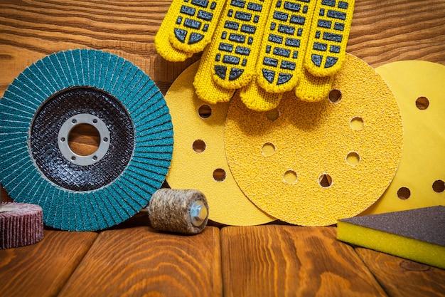 Grande conjunto de ferramentas abrasivas e luvas de trabalho amarelo no assistente de tábuas de madeira vintage é usado para moer itens