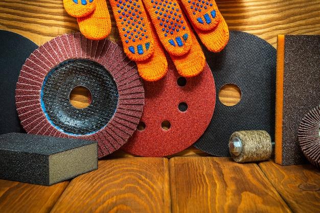 Grande conjunto de ferramentas abrasivas e luvas de trabalho laranja no assistente de tábuas de madeira vintage é usado para moer itens