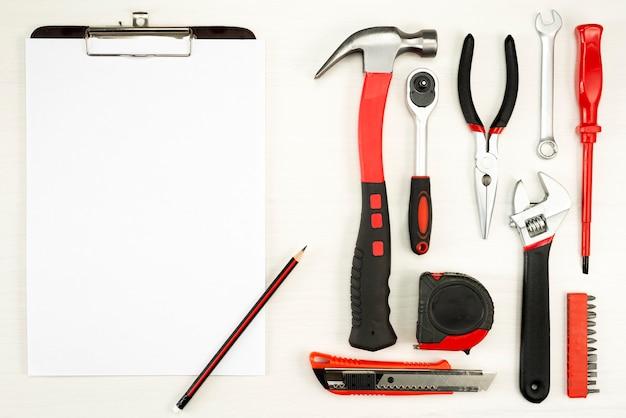 Grande conjunto de ferramentas de construção com uma folha de papel branco com um lápis em uma parede branca, vista superior
