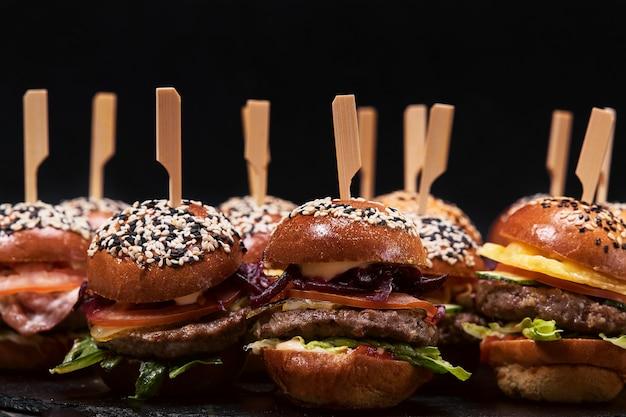 Grande conjunto de muitos hambúrgueres, cheeseburgers dispostos sobre uma mesa em uma parede escura.