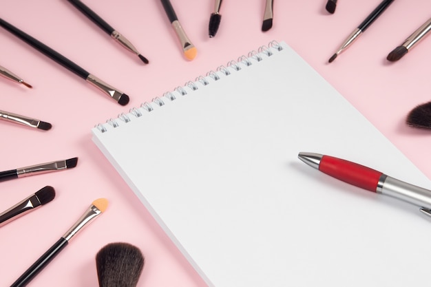 Grande conjunto de pincéis de maquiagem com uma maquete de caderno e caneta em um fundo rosa. postura plana
