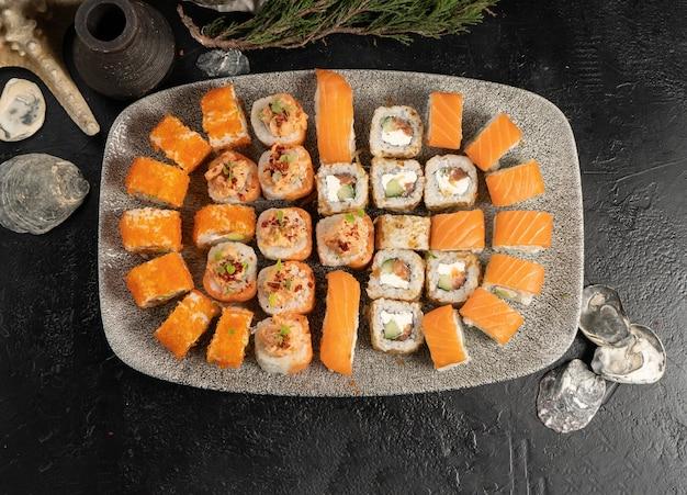Grande conjunto de sushi de rolos e nigiri com salmão e caviar de peixe voador