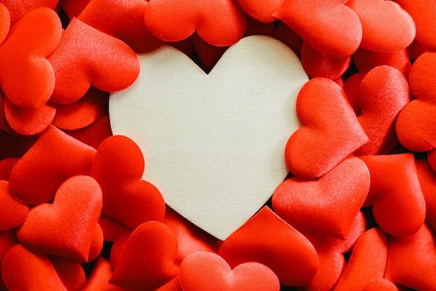 Grande coração de madeira vazio cercado por pequenos corações vermelhos para dia dos namorados, espaço livre para o texto.