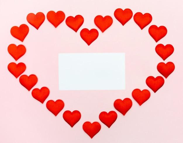 Grande coração de pequenos corações com uma folha de papel dentro da maquete em uma parede rosa. conceito de feriados e dia dos namorados.