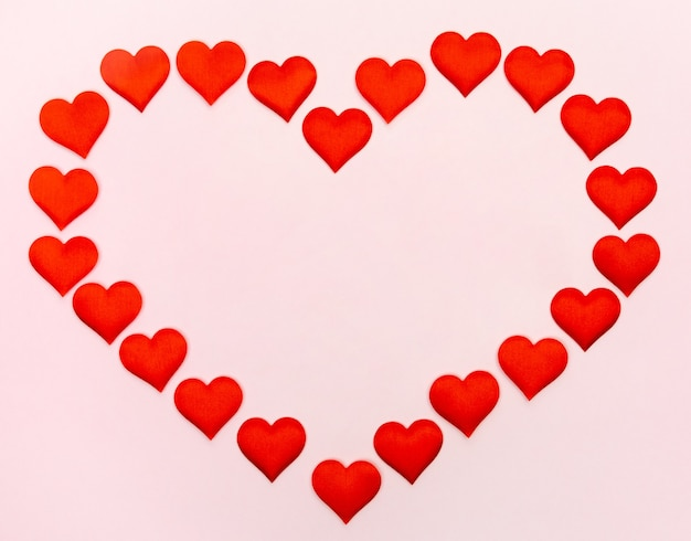 Grande coração de pequenos corações em uma parede rosa. conceito de feriados e dia dos namorados.