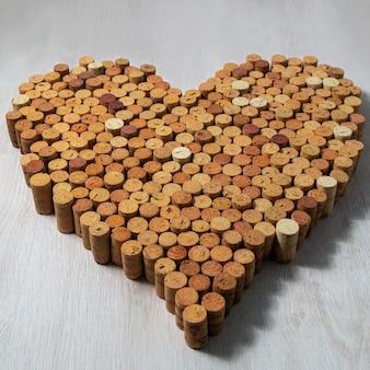 Grande coração feito de rolhas de cortiça em fundo de madeira, design de vinho concent