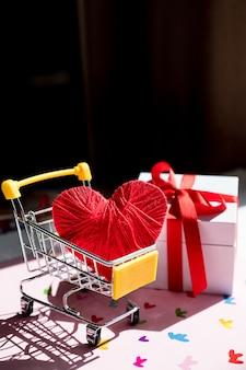 Grande coração vermelho em um carrinho de compras. conceito para comprar amor. compras online do dia dos namorados. carrinho com corações.