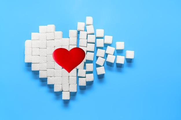 Grande coração vermelho em um coração partido feito de cubos de açúcar em um fundo azul.