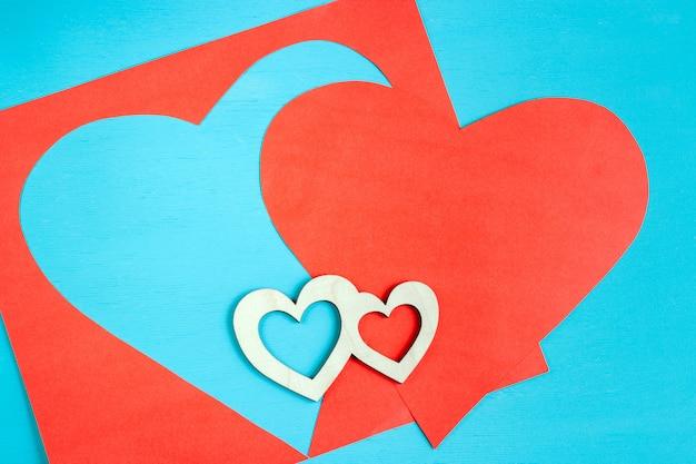 Grande coração vermelho esculpida em folha de papel e dois pequenos corações de madeira estão mentindo no azul brilhante.