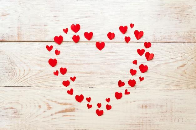 Grande coração vermelho feito de papel cortado pequenos corações no backround de madeira